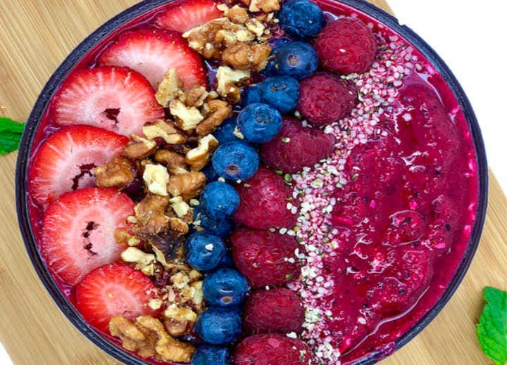 A vibrant purple smoothie bowl topped with berries and nuts.