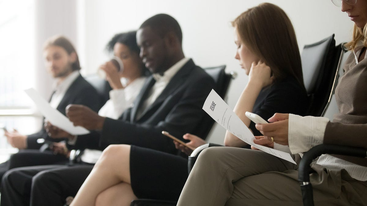 A group of people sitting in chairs looking at their resumes and phones.