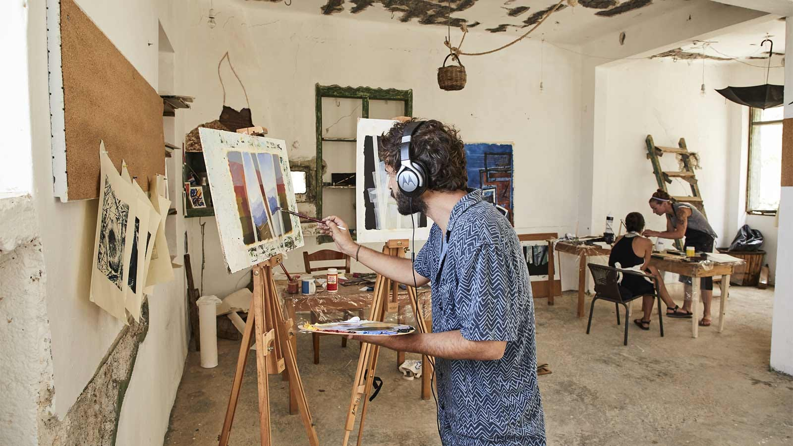 A man painting a canvas on an easel in the Mudhouse studio.