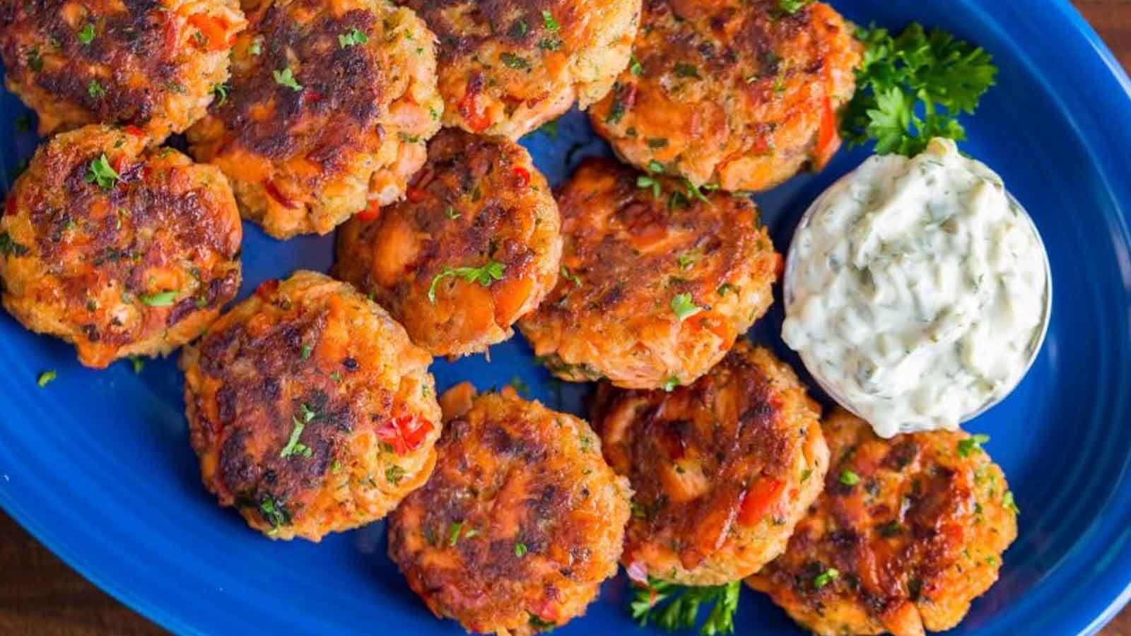 Fried salmon patties on a cobalt blue platter with tartar sauce.