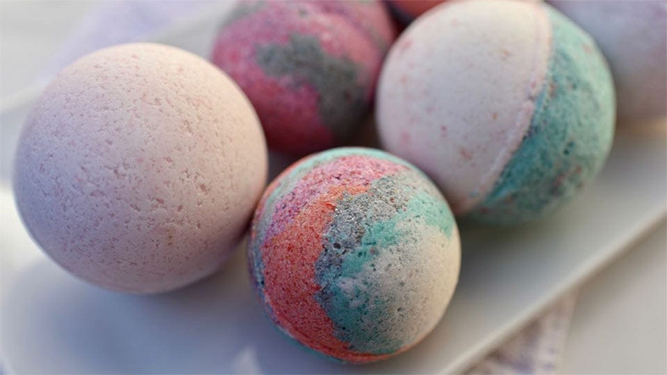 Four colorful bath bombs, sitting on a platter.
