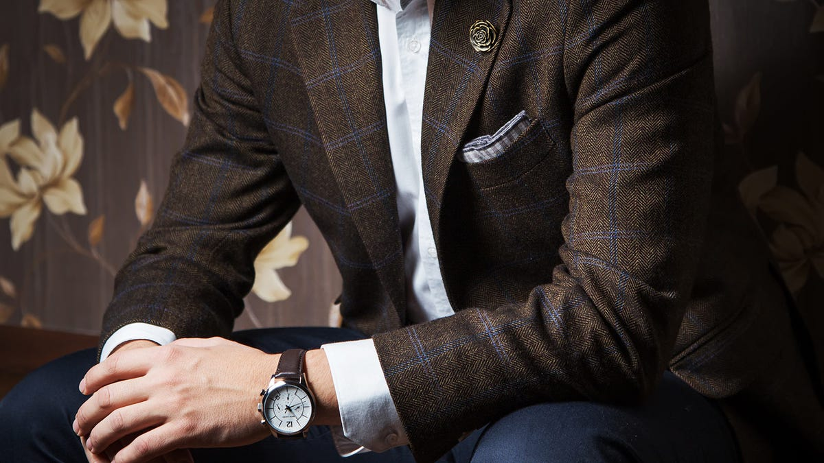 Man wearing a sport coat sitting with this hands crossed.