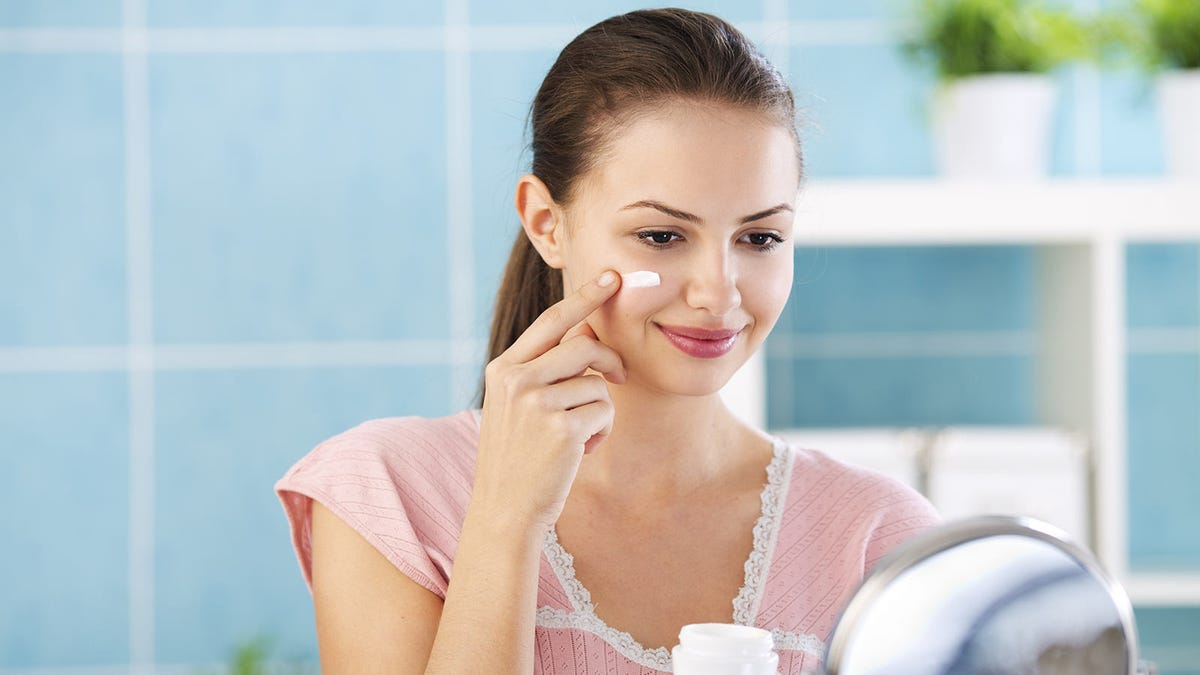 Young woman putting night time moisturizer on her face before bed.