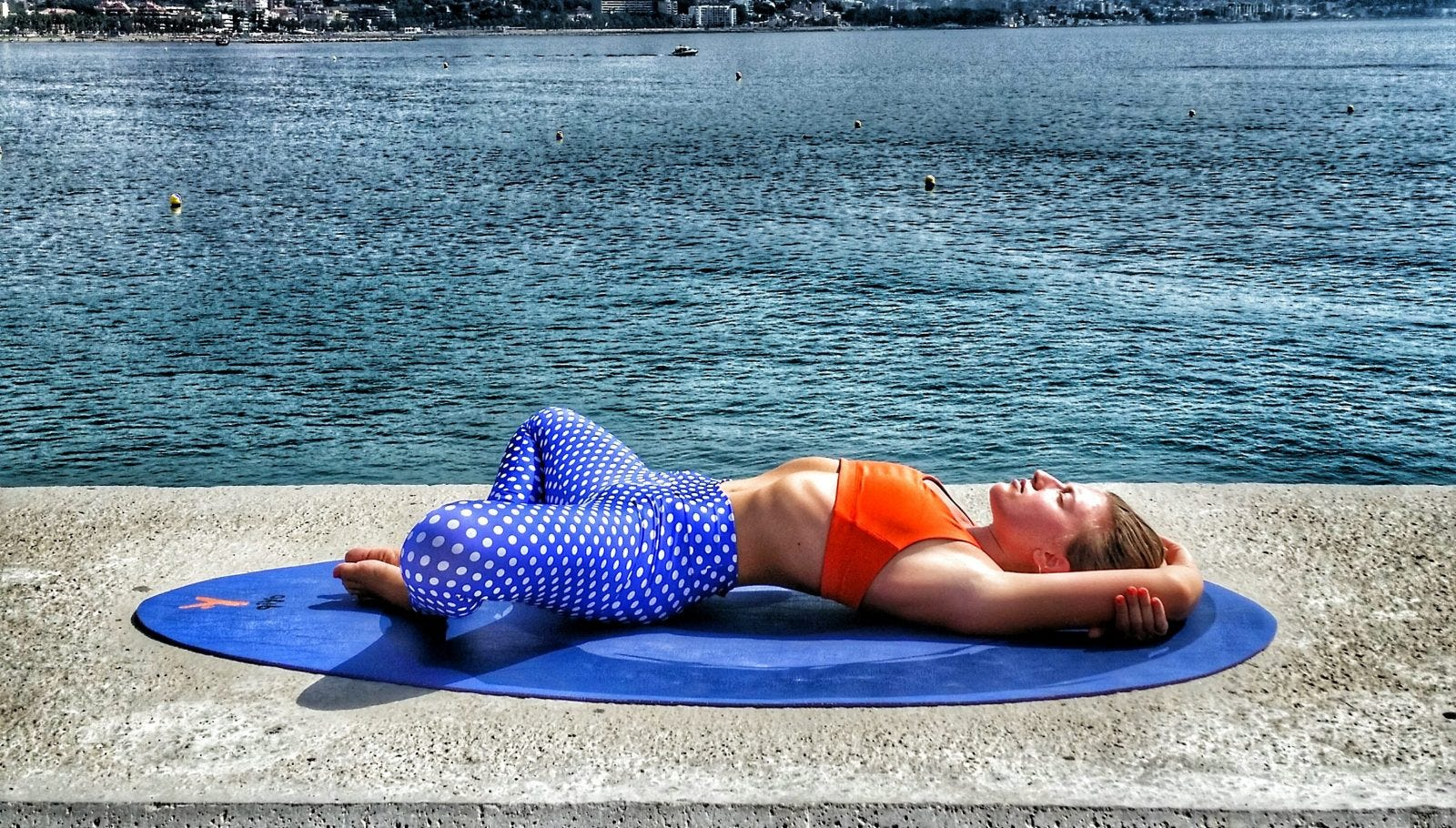 A woman in resting yoga pose in front of the ocean.