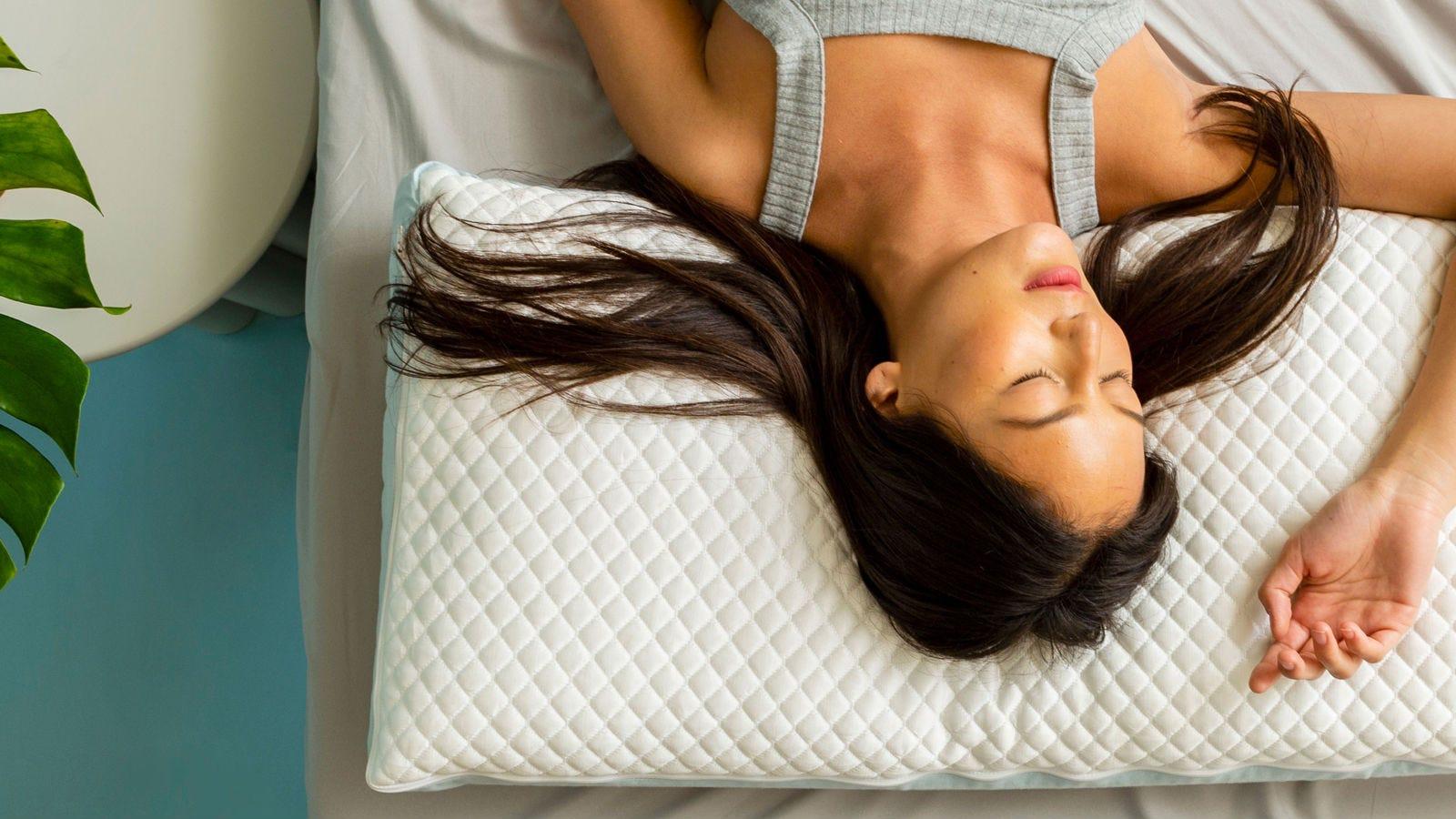 A woman asleep on a Pluto Pillow.