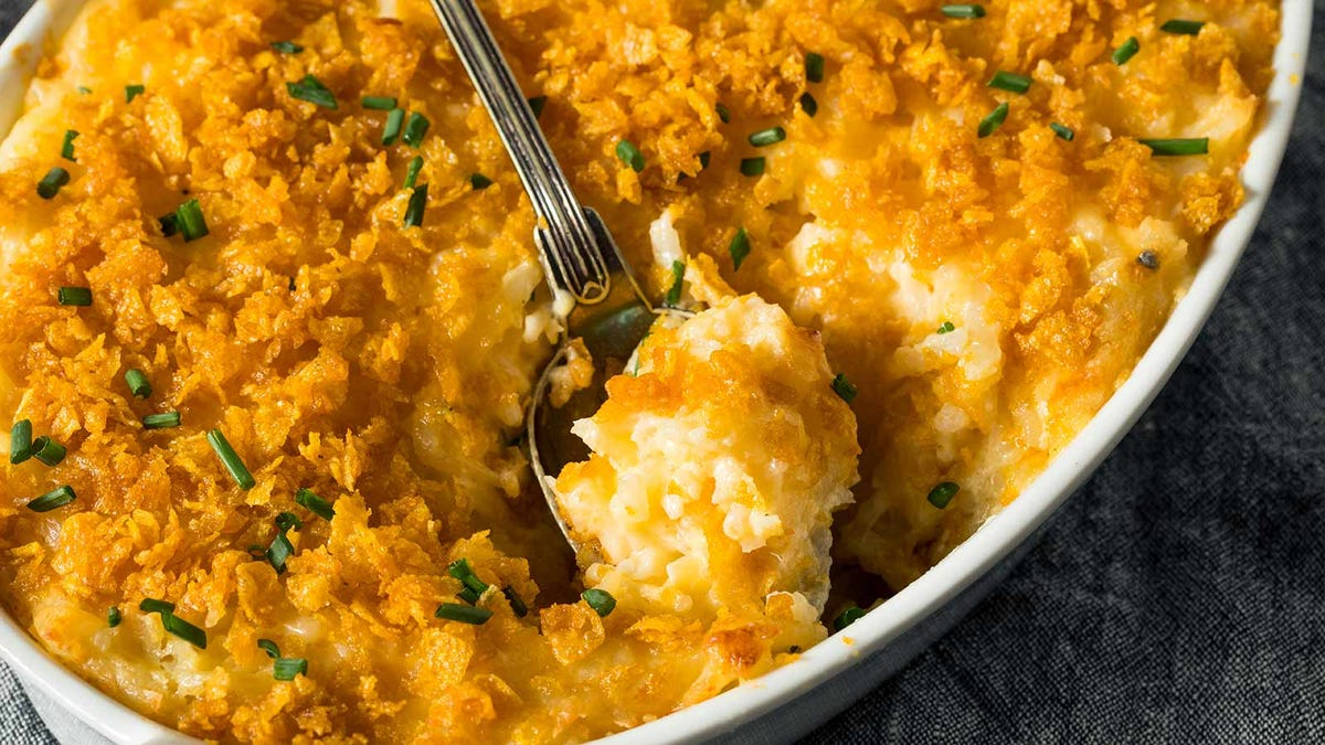 A cheesy potato casserole dish with crushed potato chips on top.