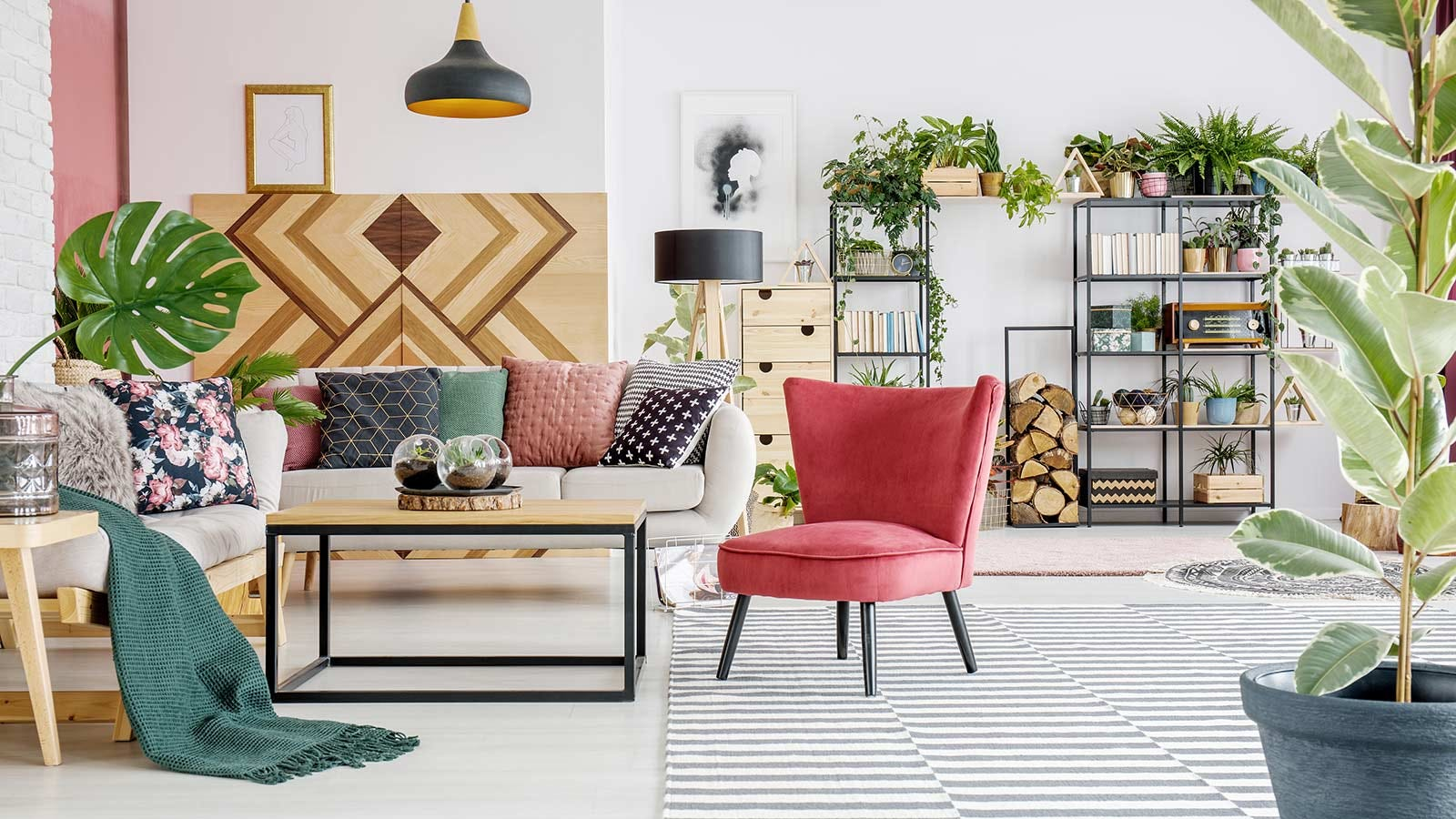 A busy but well appointed living space with plants, shelving, seating, and a wide array of colors and textures.