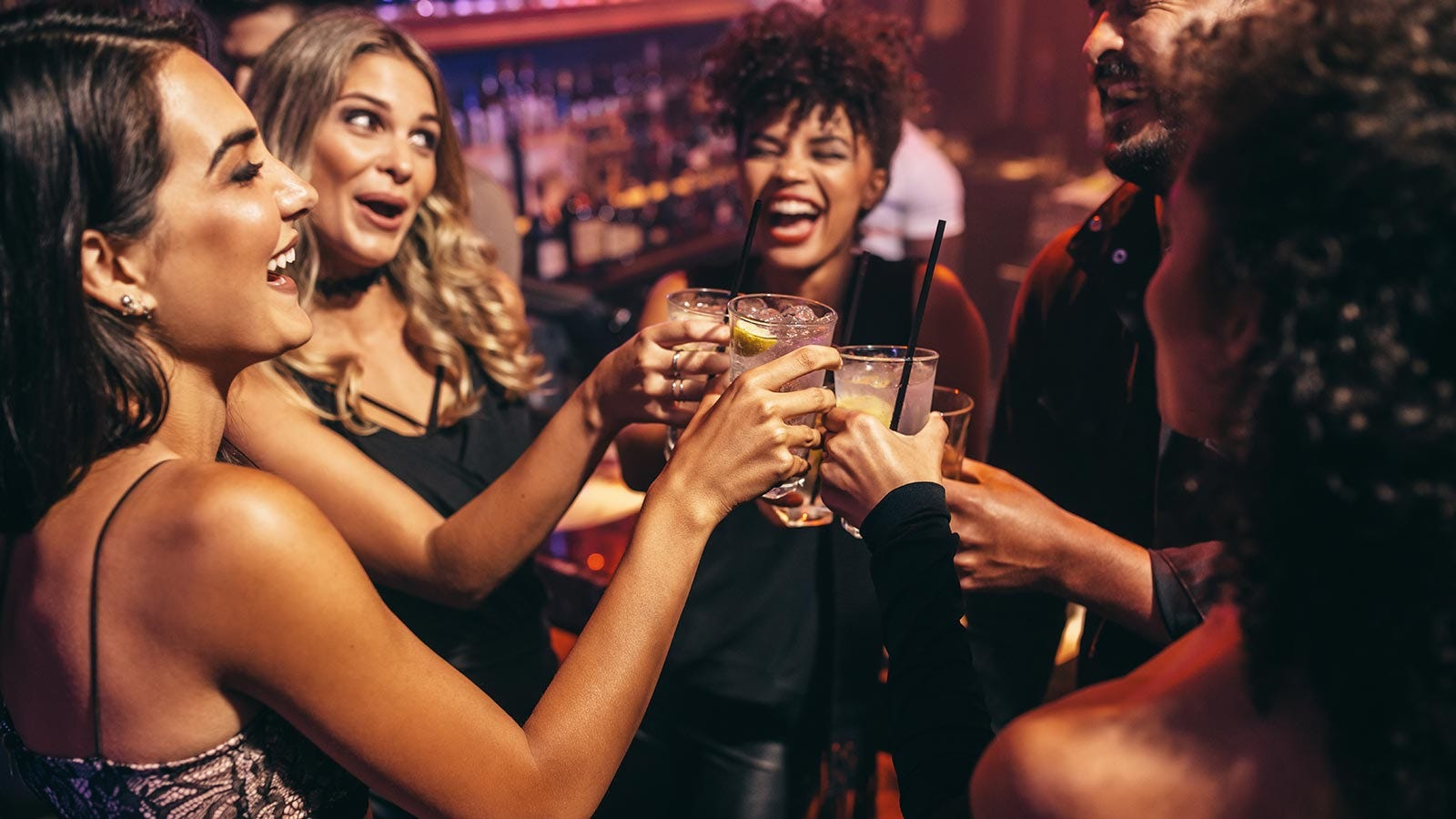 Group of people toasting with drinks at a bar.