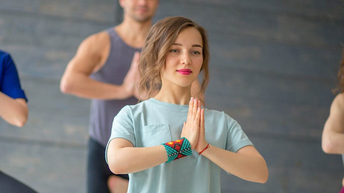 Woman practicing yoga in a group class.