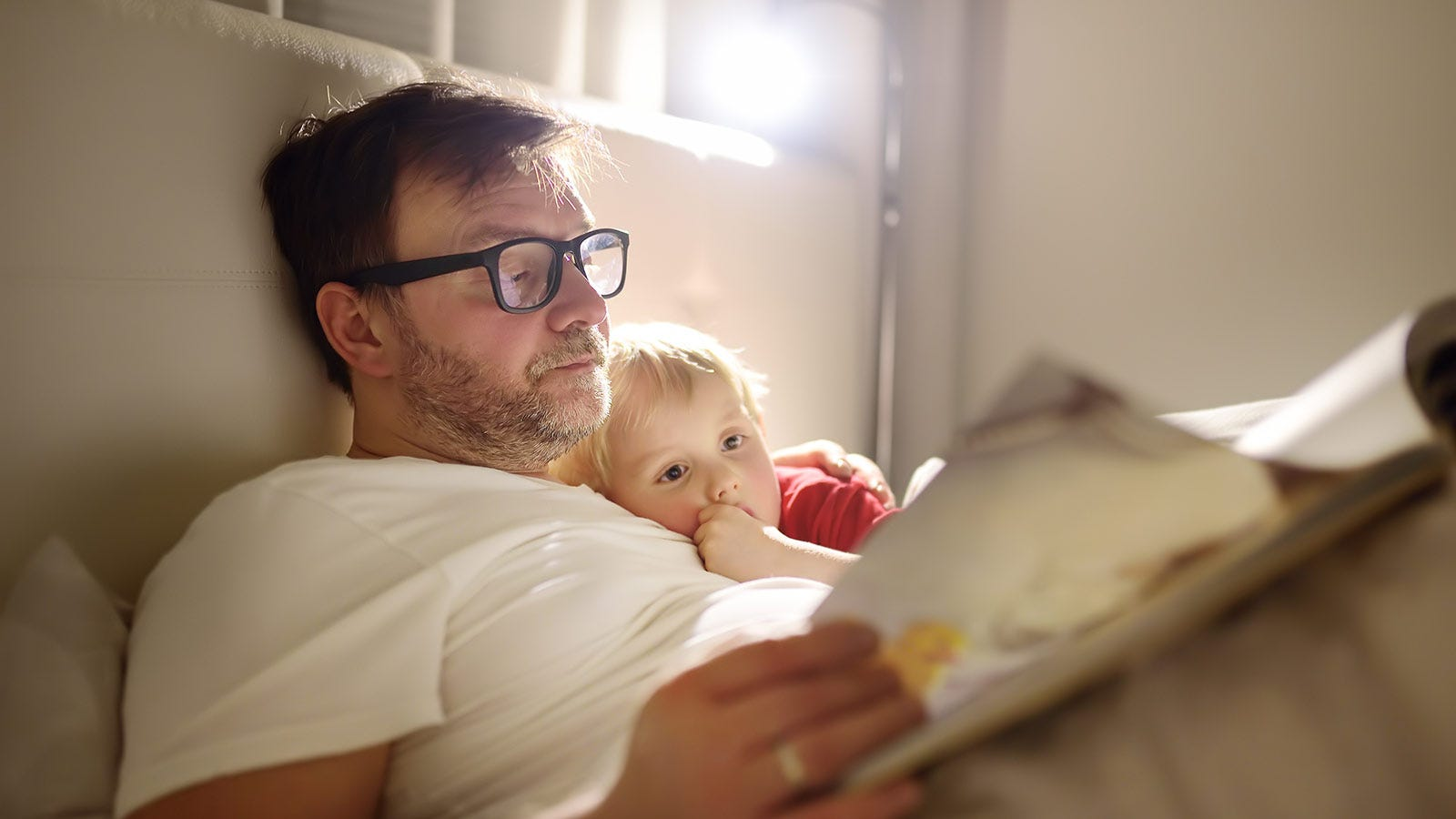 A man reading a book to a child at bedtime.