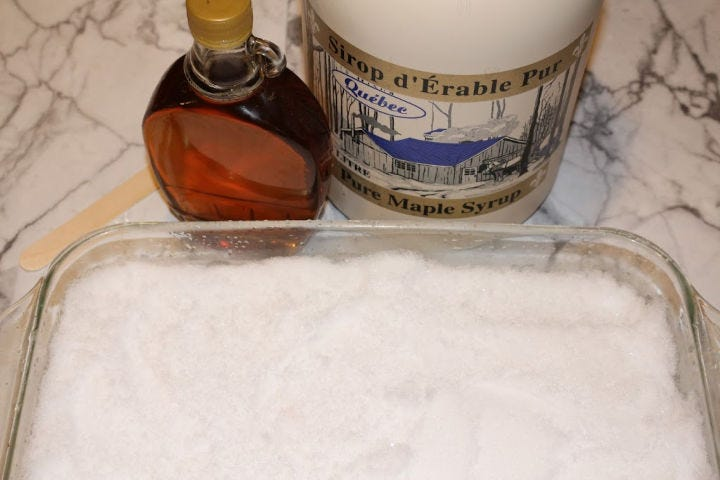 Snow packed in a casserole dish sitting next to two bottles of maple syrup.