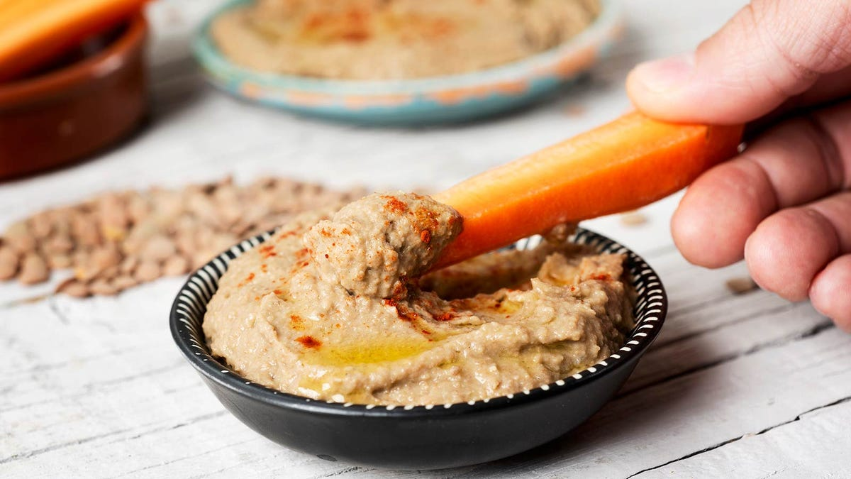 Man dipping sliced carrots in fresh hummus.