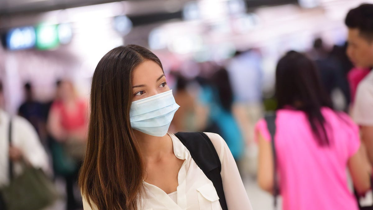 Woman in a crowd wearing a surgical mask.