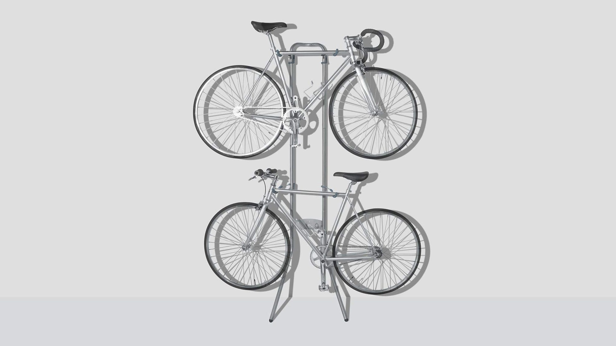 The Delta Cycle Michelangelo Bike Rack standing against a wall holding two bicycles.