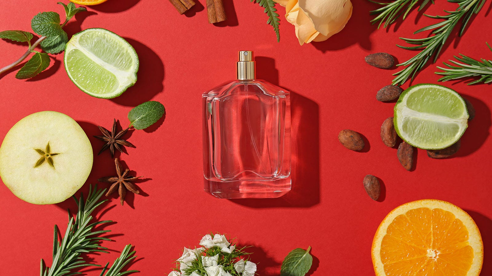 An empty perfume bottle surrounded by fruits, nuts, and green sprigs.