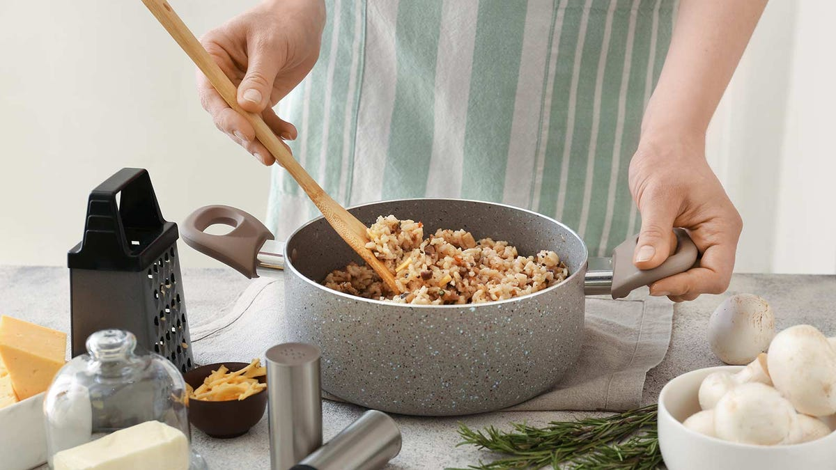Cooking up a big pot of risotto with extra ingredients.