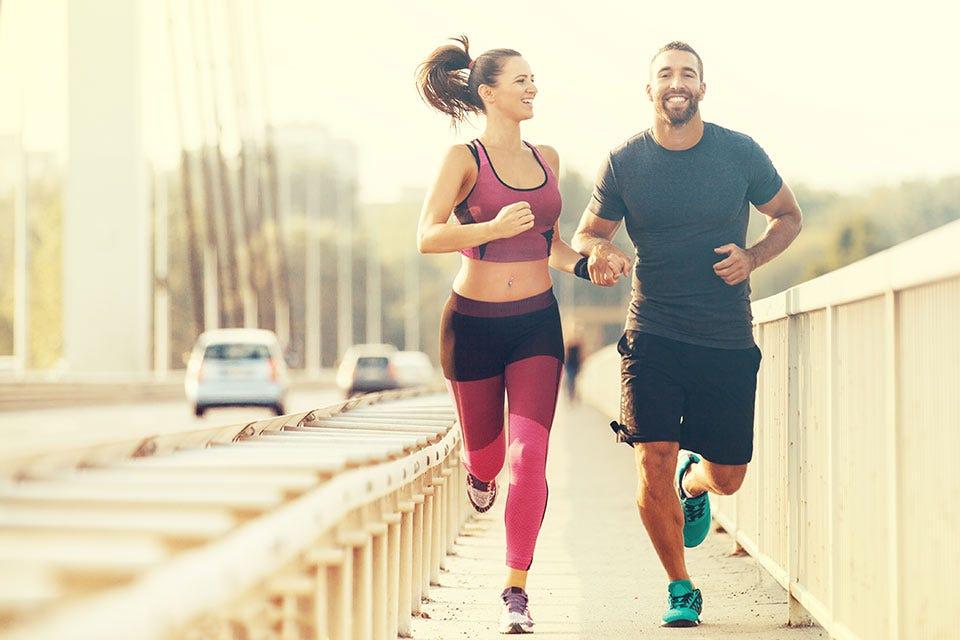 A man and woman running across a city bridge.