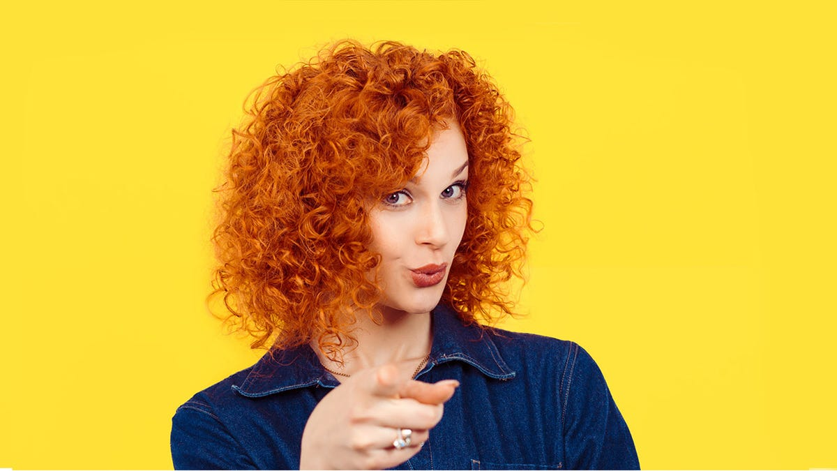 A red-haired woman puckering her lips and pointing at the viewer in a mischievous way.