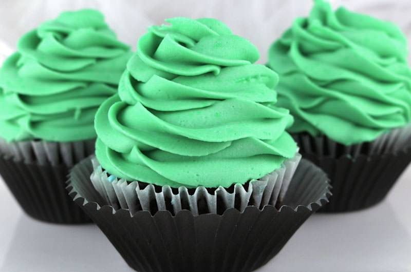 Three cupcakes covered with green, rose-shaped mint buttercream icing.