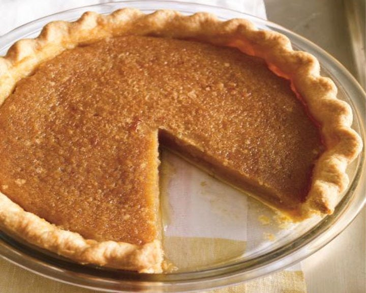 A Maple Syrup Pie on a glass platter with one piece missing.