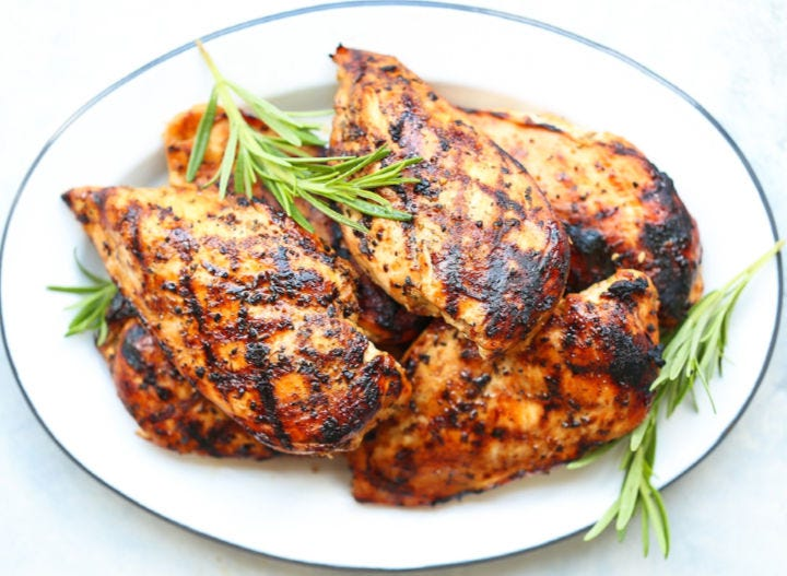 An oval platter piled with maple rosemary grilled chicken breasts.