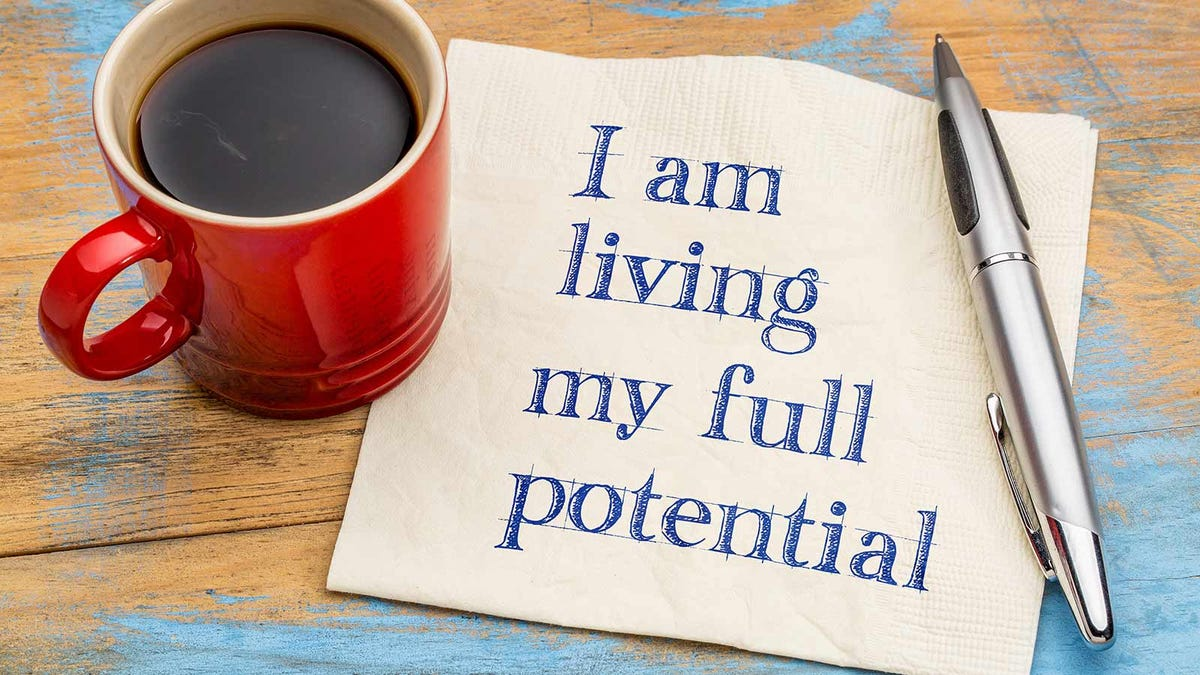 """""""I am living my full potential"""" written on a napkin sitting next to a mug of coffee and a pen."""