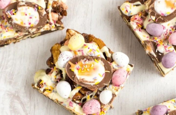 Four squares of Crème Egg Rocky Road, each topped with Cadbury mini eggs and a Cadbury Crème egg.
