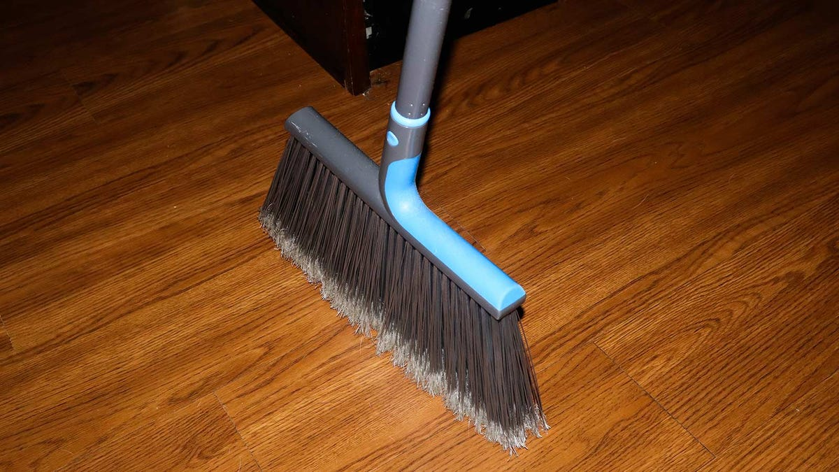 A broom standing on its own with the support of its bristles.