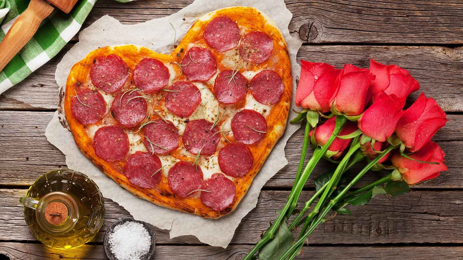A heart-shaped pepperoni pizza on a wooden table next to a bouquet of roses.
