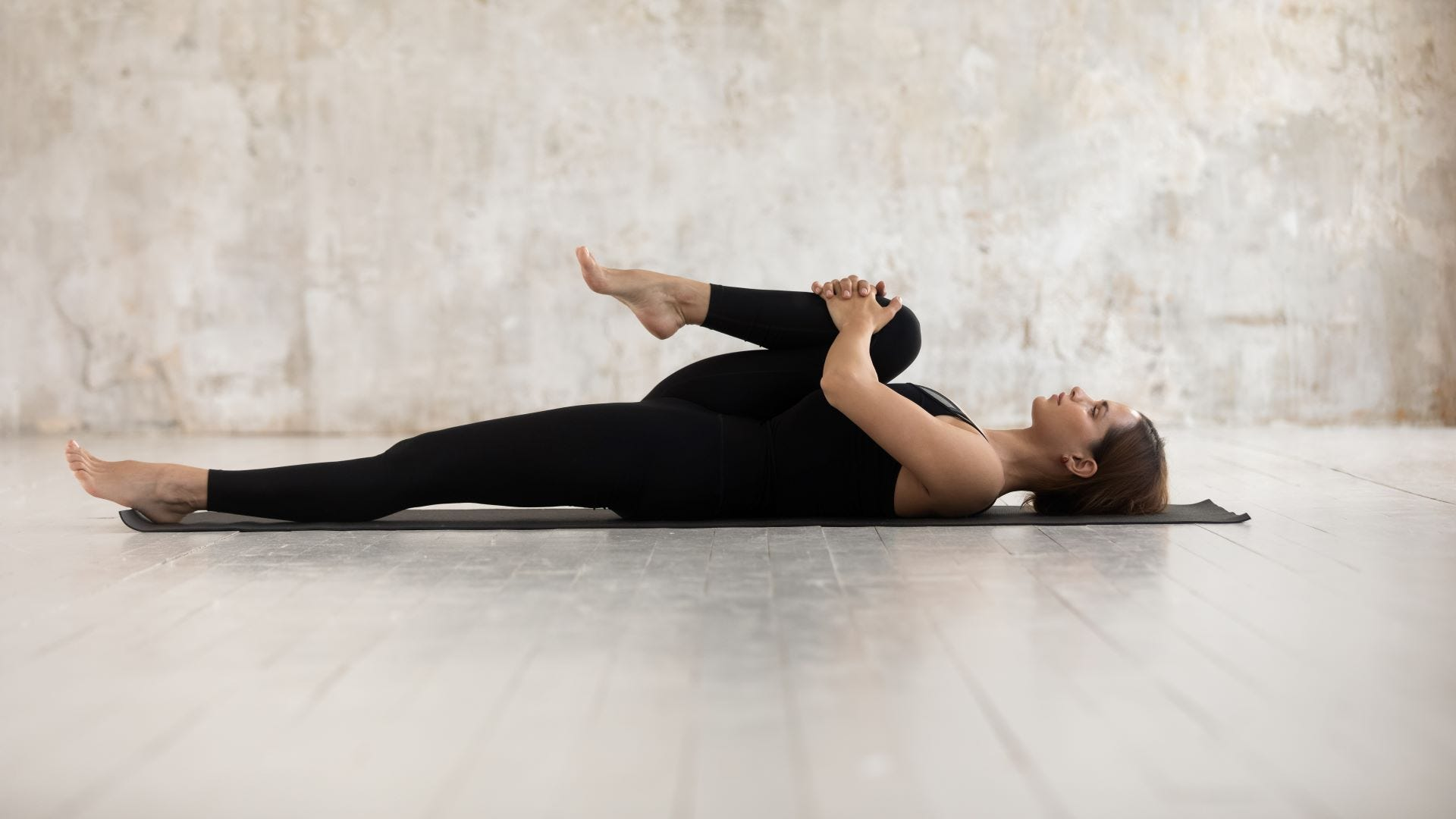 A woman lying on her back on a yoga mat clutching one knee to her chest.