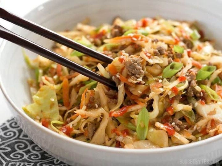 A pair of chopsticks holding a bite of cabbage stir-fry over a bowl full of it.