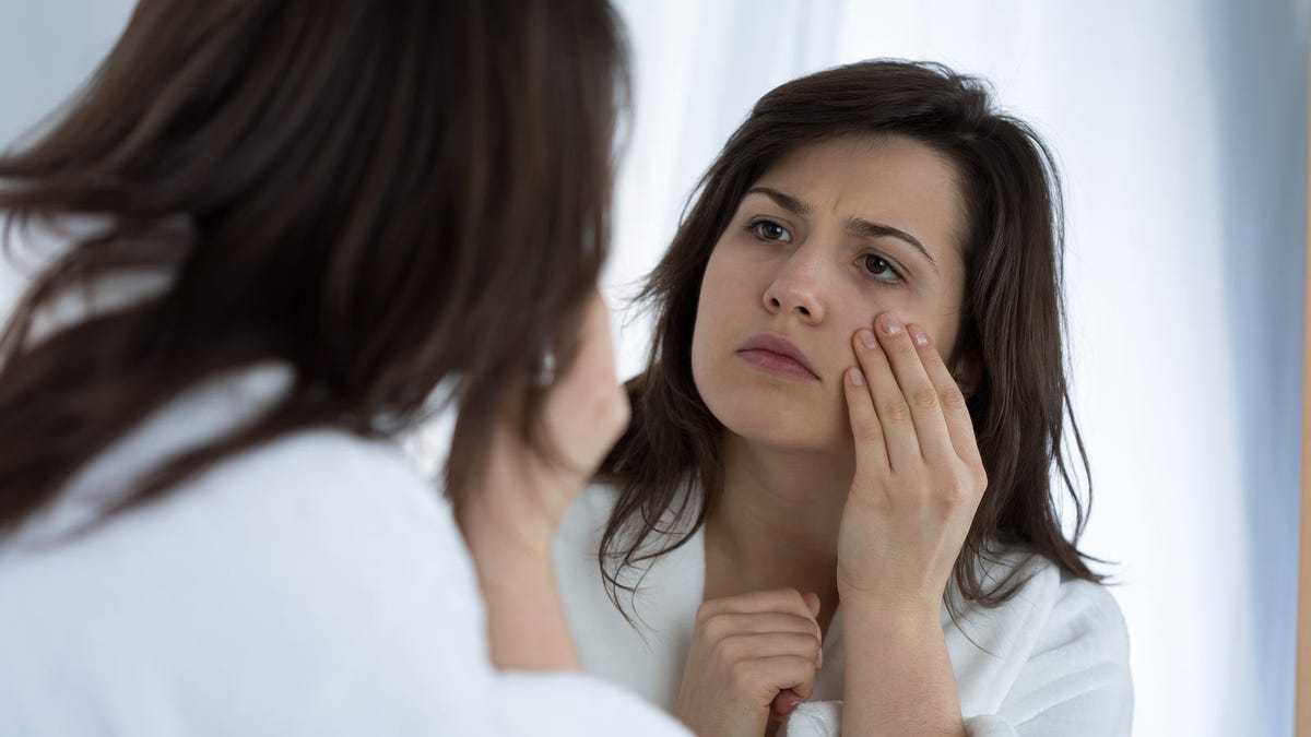 A woman looking at under-eye circles in a mirror.