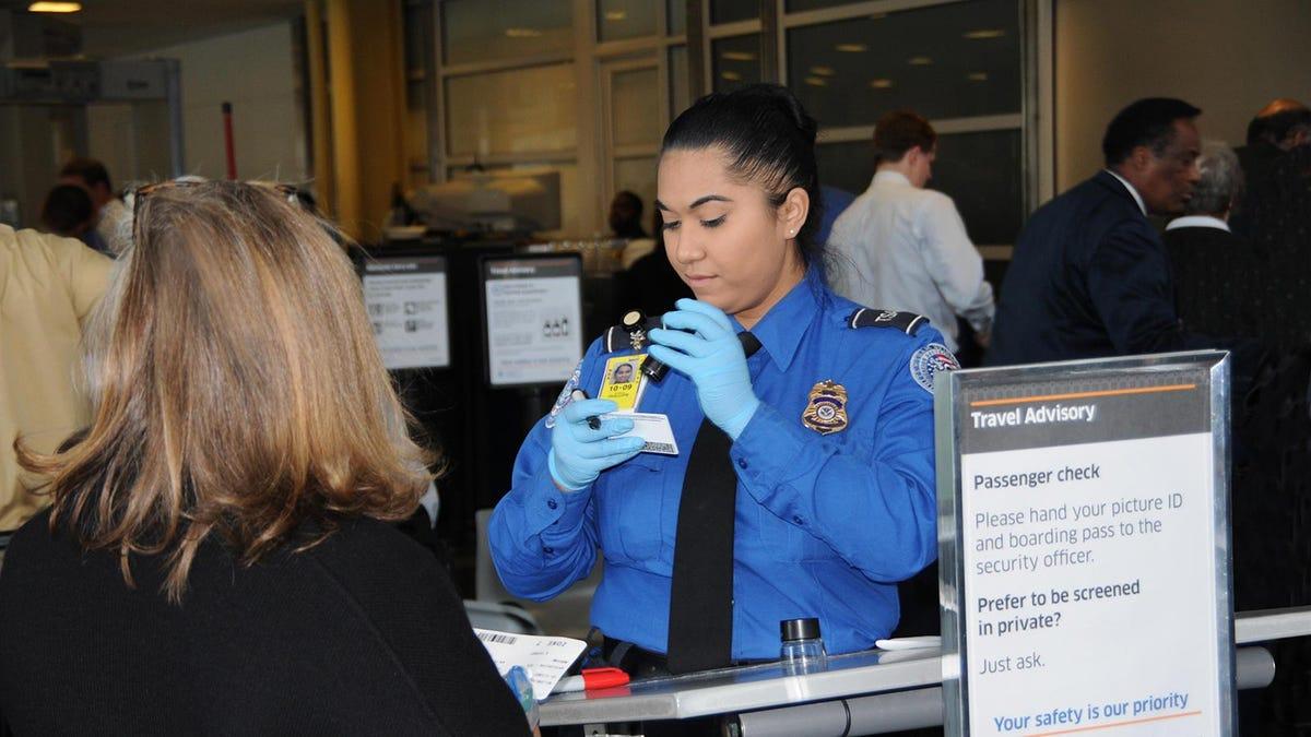 A TSO checking the ID of a traveler.