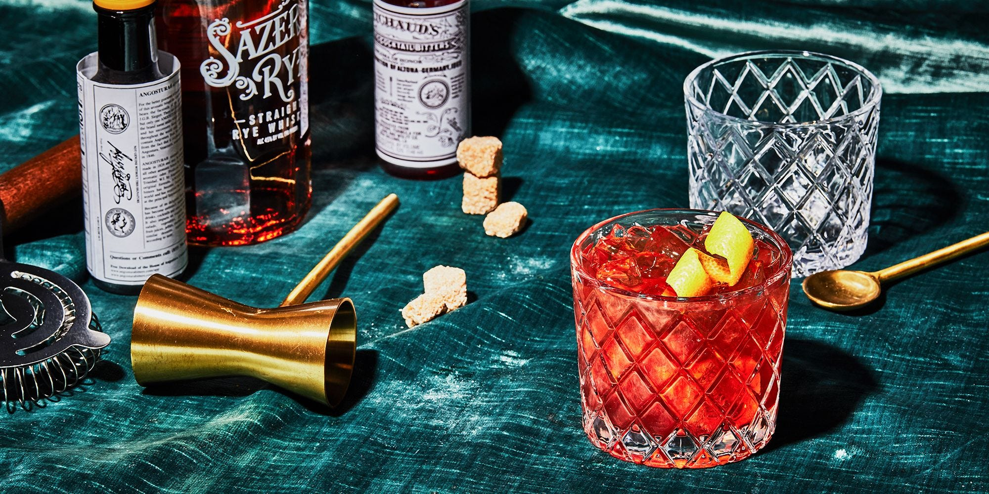 A table top set up with the fixings of a Sazerac cocktail.