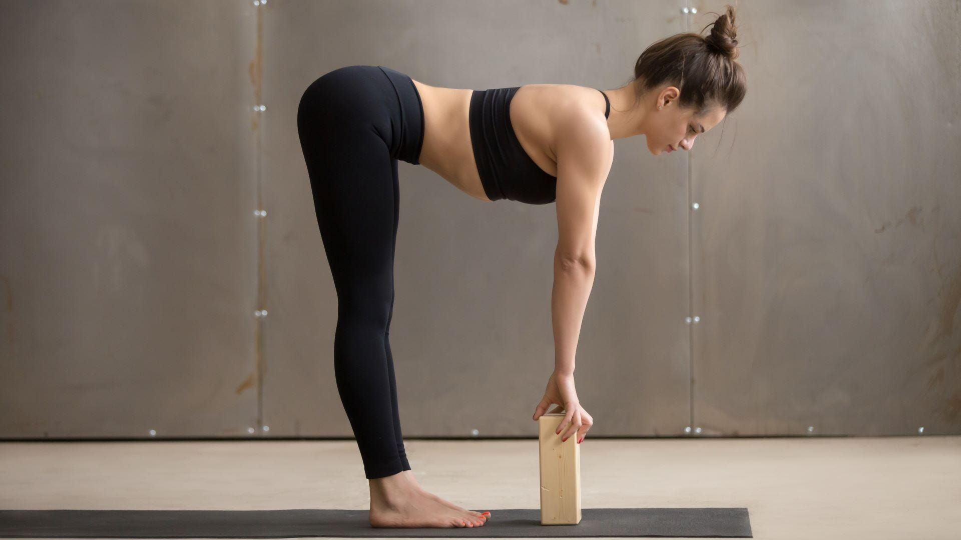 A woman doing a forward fold yoga pose with a yoga brick.