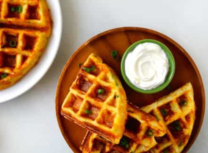 Freshly made mashed potato waffles with a dipping sauce.