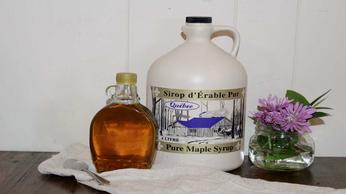 A classic glass serving bottle full of maple syrup sitting next to a four-liter jug of Pure Maple Syrup from Québec.