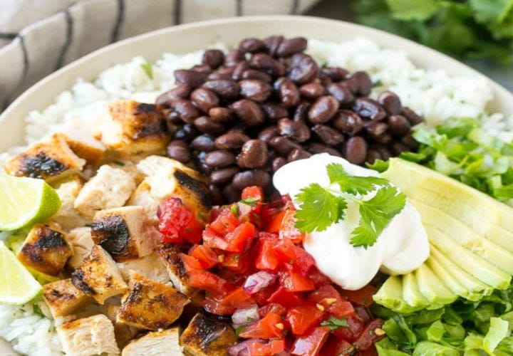 A burrito bowl filled with chicken, avocado, tomatoes, black beans and sourcream.