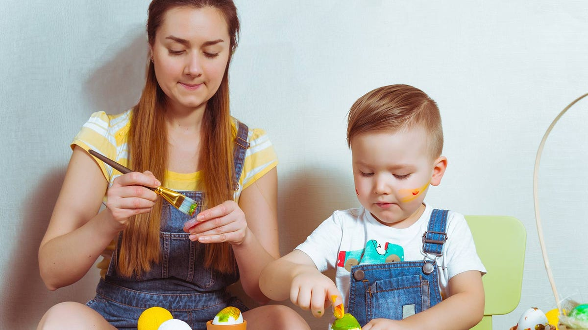A teenager girl and a young boy painting some Easter crafts.