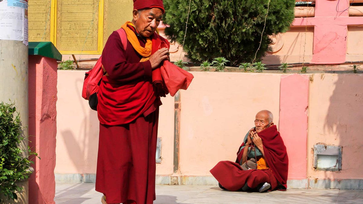 Two monks greeting each other in passing.