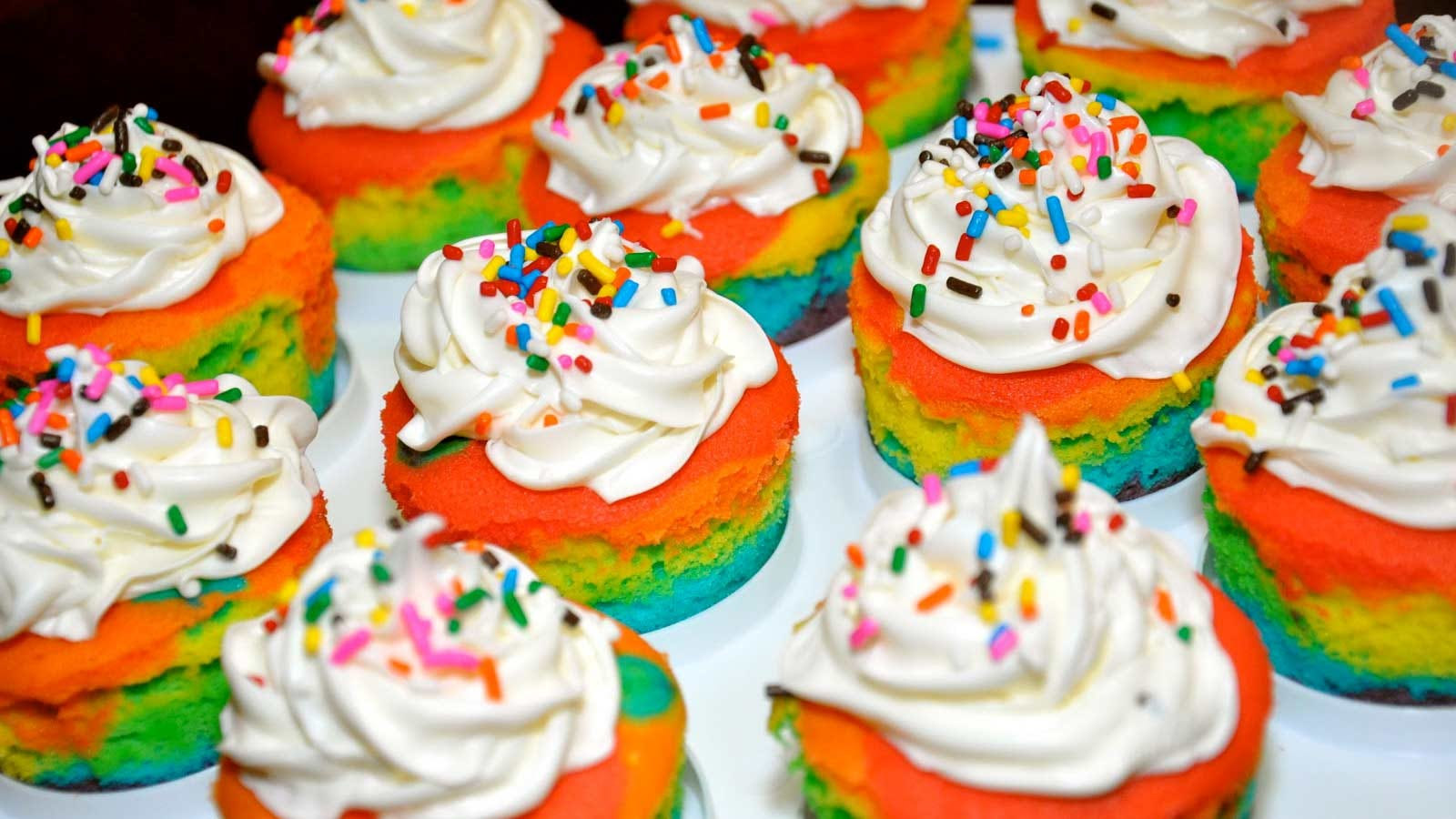 Colorful cupcakes, decorated with white frosting and sprinkles.