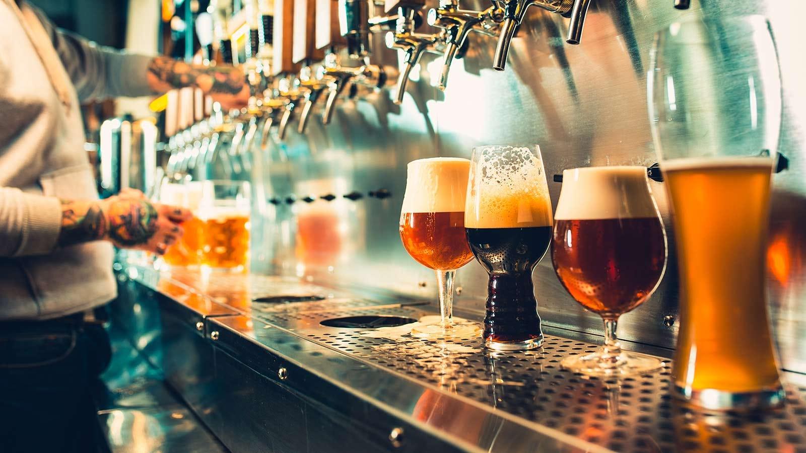 Bar tender filling up different kinds of beer glasses.