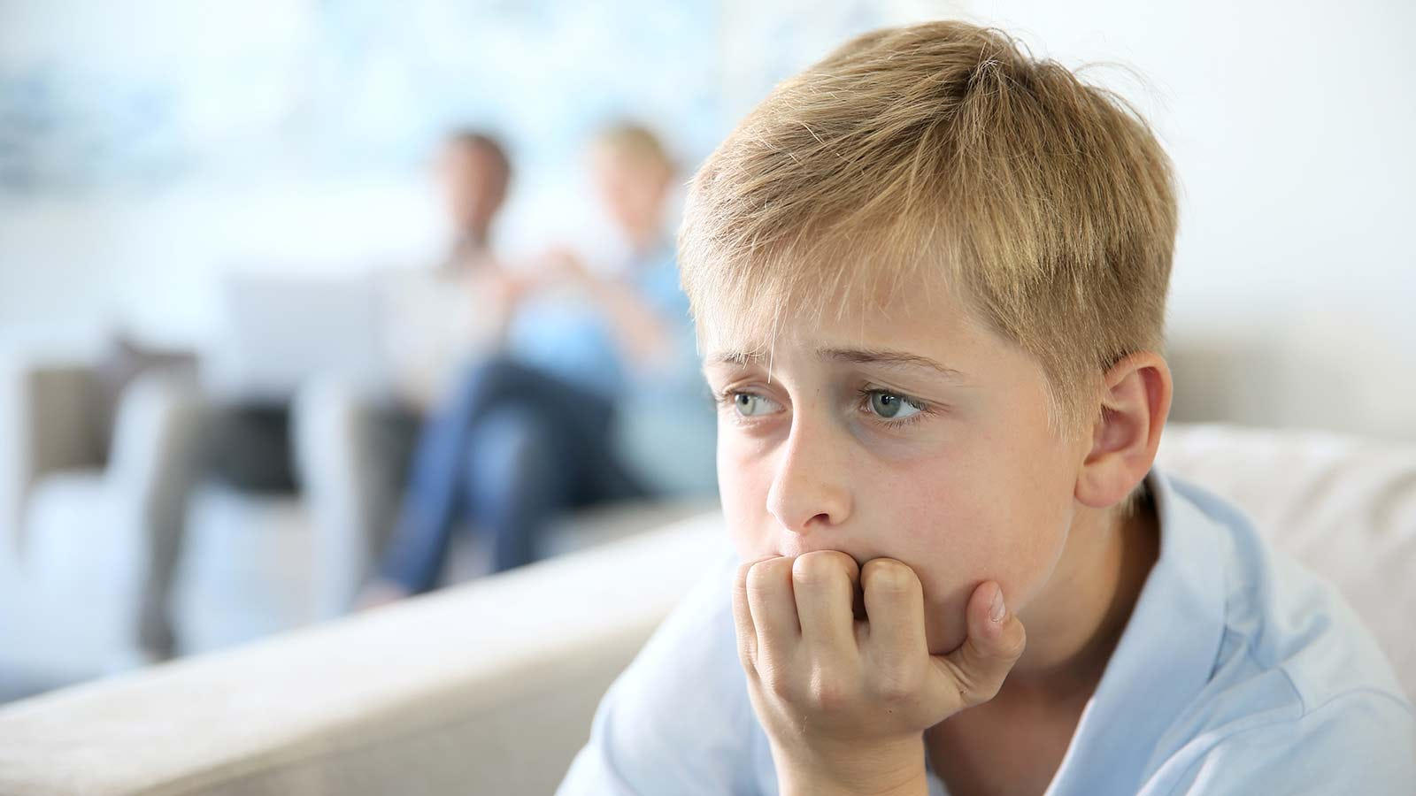 Worried boy, sitting in his living room with his parents.