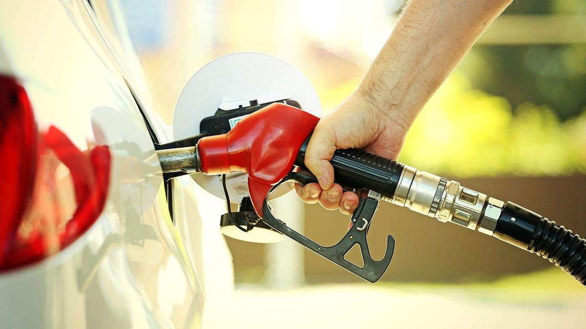 Man pumping gas, touching a germ-laden pump handle.
