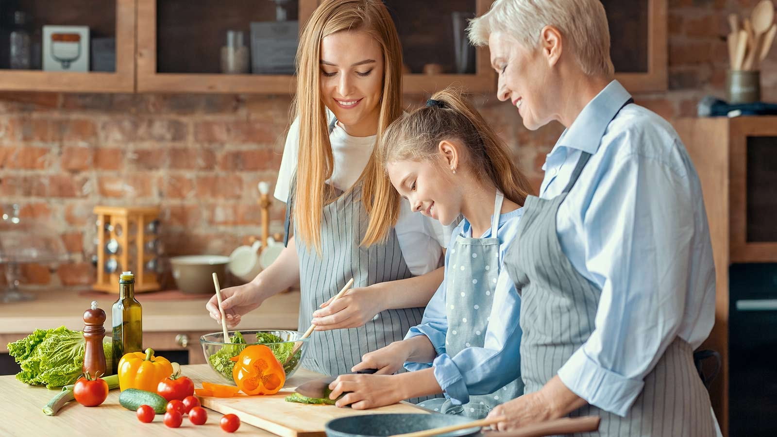 Mother and grandmother, helping a tween girl prepare a meal in a sunny kitchen.
