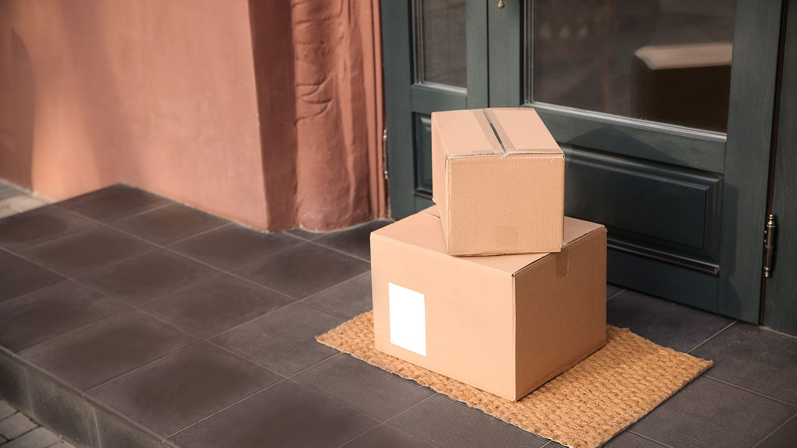 Two cardboard boxes sitting on a porch.