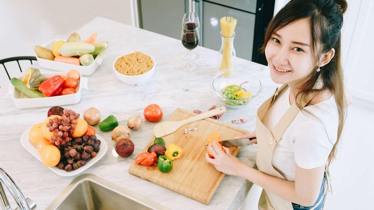Teenage girl helps prepare dinner by chopping vegetables.
