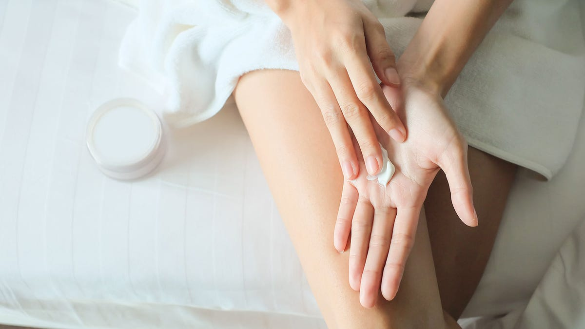 Woman applying cream to her hands before bed.