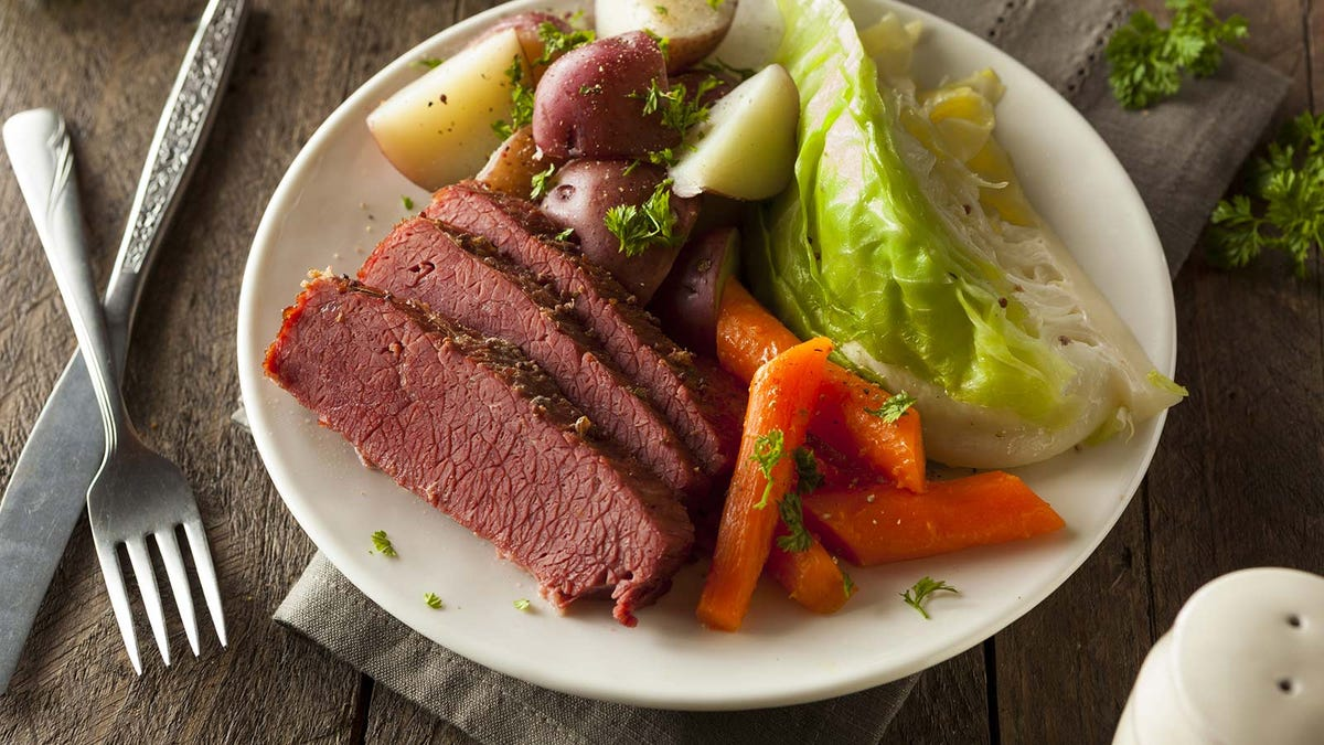 A plate of corned beef, cabbage, potatoes, and carrots.