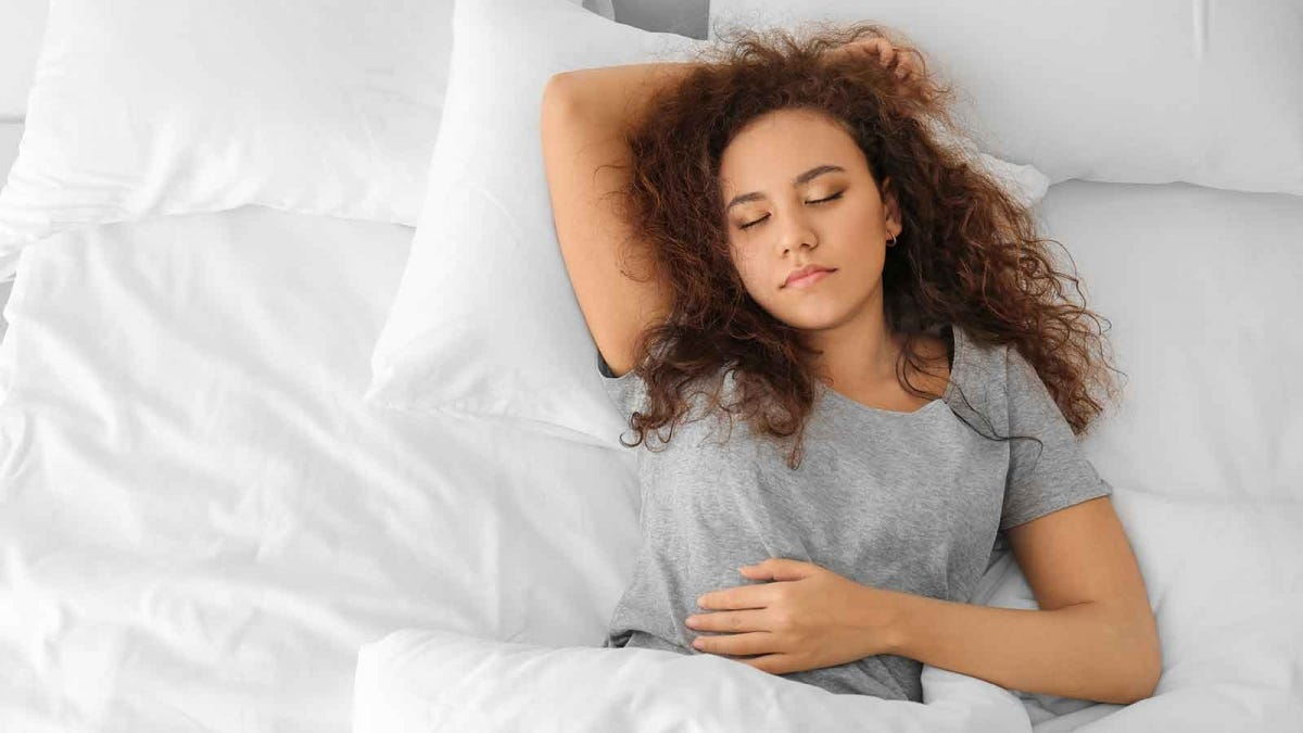 Woman sleeping in bed, surrounded by crisp white linens.